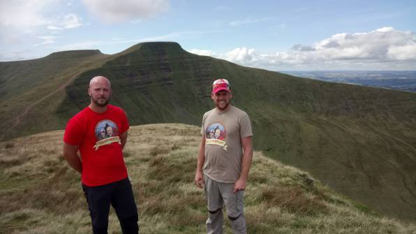 Pen Y Fan in th ebackground as Summit or Nothing stand on top of Crybyn